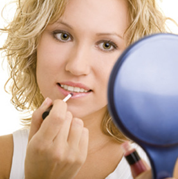 Woman staring in mirror putting on lipstick